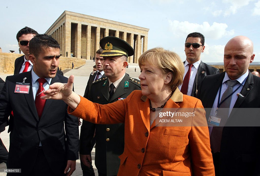German Chancellor Angela Merkel (C) gestures as she visits the mausoleum of Turkey's Republic's founder Kemal Ataturk in Ankara, on February 25, 2013, on the second an final day of her official visit to Turkey. AFP PHOTO ADEM ALTAN