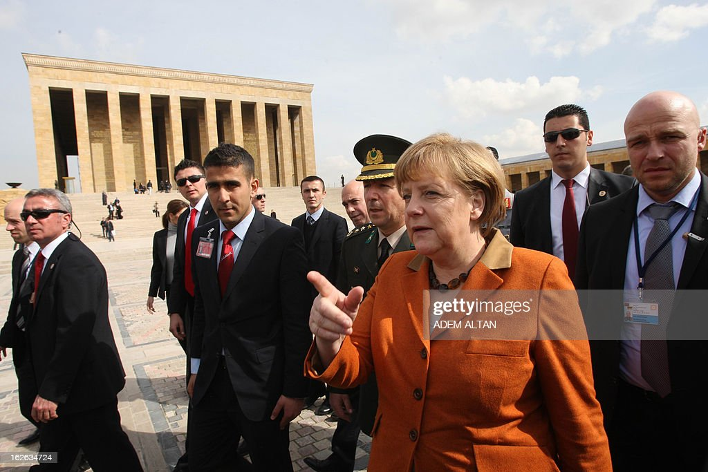 German Chancellor Angela Merkel (C) gestures as she visits the mausoleum of Turkey's Republic's founder Kemal Ataturk in Ankara, on February 25, 2013, on the second an final day of her official visit to Turkey.
