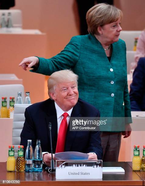 German Chancellor Angela Merkel gestures behind US President Donald Trump ahead the third working session 'Partnership with Africa' on the second day...