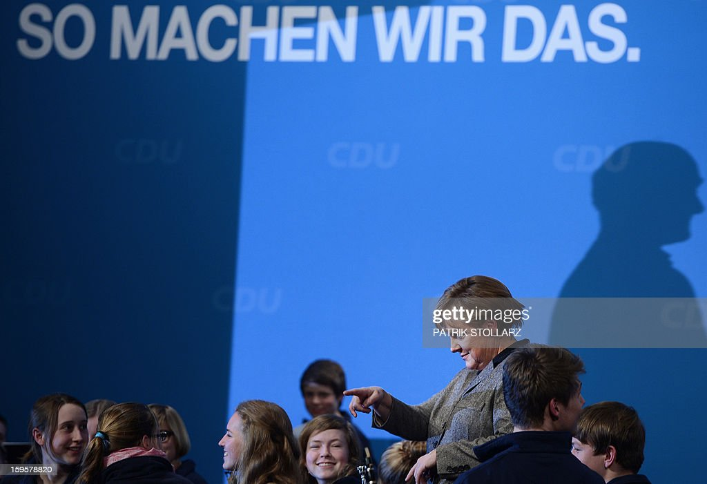 German Chancellor Angela Merkel gestures next to a youth orchestra in front of a placard saying 'we do it like this' after a speech during an election campaign event of the regional Christian Democratic Union (CDU) party for the 2013 state elections in Osnabrueck, northern Germany, on January 16, 2013.