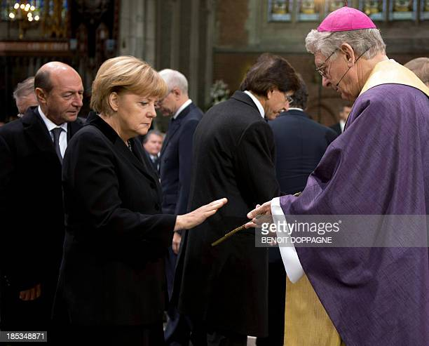 German Chancellor Angela Merkel gestures next to Bishop Luc Van Looy during the funeral ceremony of Belgian Minister of State Wilfried Martens on...