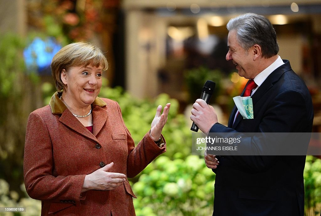 German Chancellor Angela Merkel (L) gestures to Berlin Mayor Klaus Wowereit (R) on January 18, 2013 during the opening of the Green Week Agricultural Fair in Berlin.