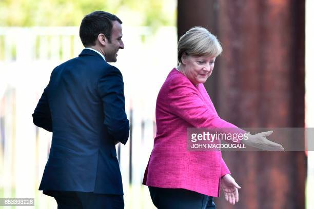 German Chancellor Angela Merkel gestures to French President Emmanuel Macron on May 15 2017 at the chancellery in Berlin / AFP PHOTO / John MACDOUGALL