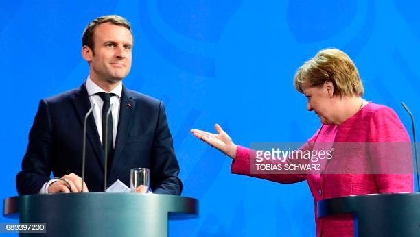 TOPSHOT German Chancellor Angela Merkel gestures to French President Emmanuel Macron after addressing a press conference at the chancellery in Berlin...