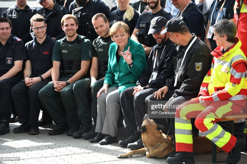 TOPSHOT - German Chancellor Angela Merkel (C) gestures towards a police dog as she poses with policemen who were deployed during the G20 summit in Hamburg, northern Germany, on July 8, 2017. / AFP PHOTO / POOL / Patrik STOLLARZ