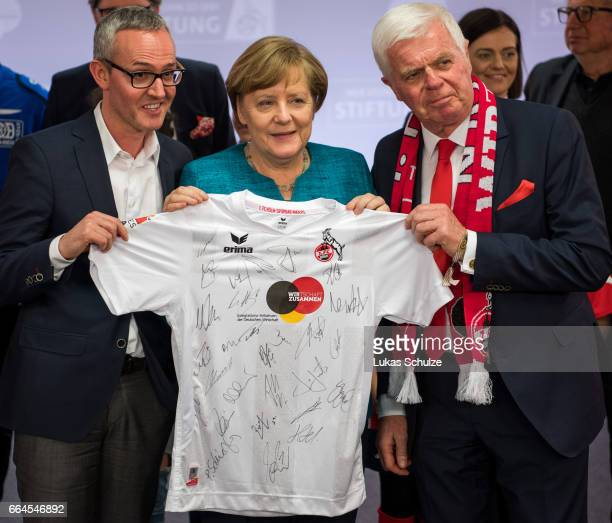 German Chancellor Angela Merkel gets an jersey of the team from Werner Spinner President of 1 FC Koeln after a meeting with members of the 1 FC Koeln...