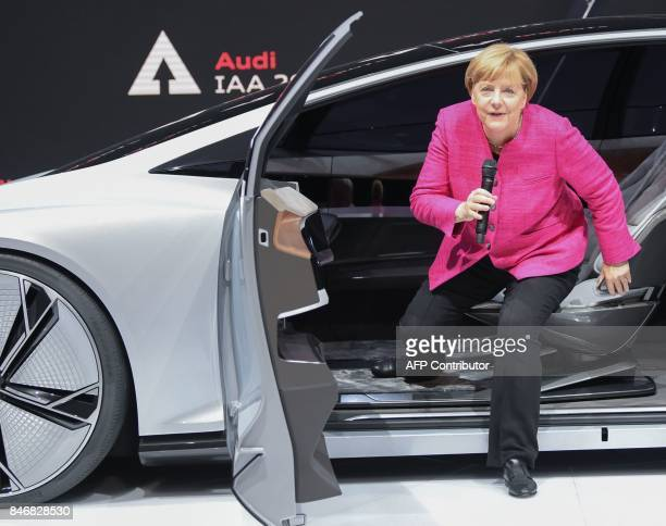German Chancellor Angela Merkel gets out of a Audi Aicon autonomous concept car as she visits the booth of Audi during her inauguration tour of the...