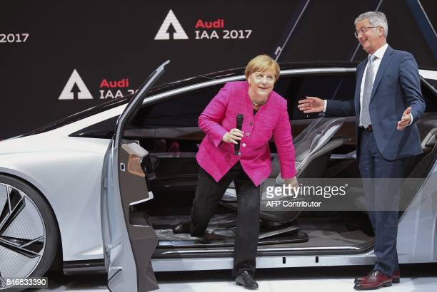 German Chancellor Angela Merkel gets out of a Audi Aicon autonomous concept car as Audi CEO Rupert Stadler watches during her inauguration tour of...