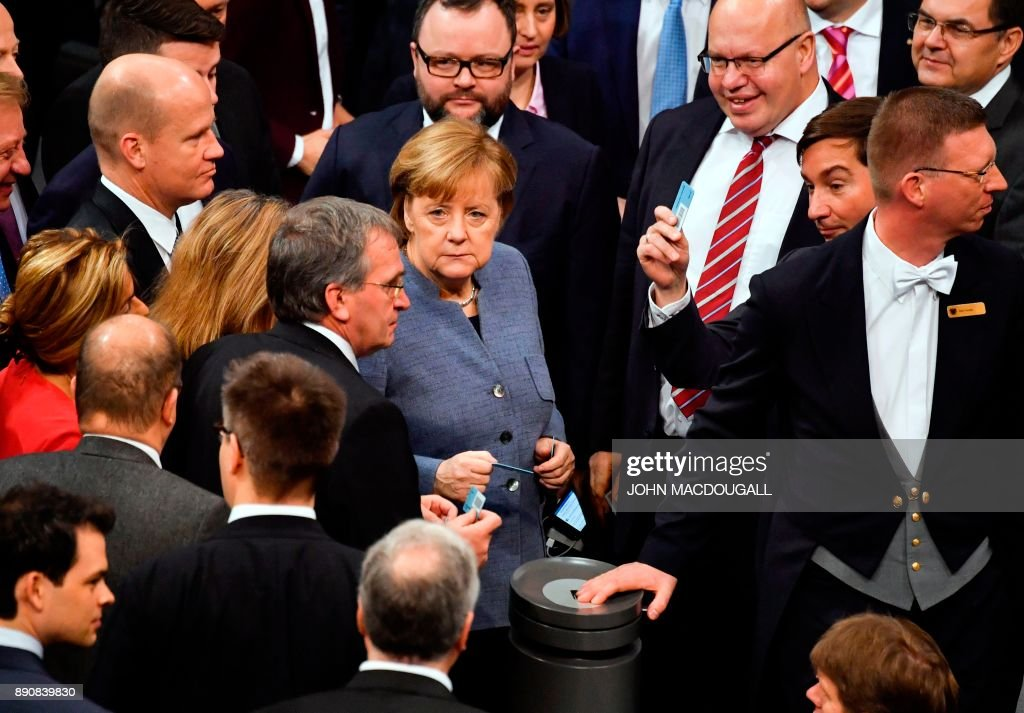 German Chancellor Angela Merkel (C) gets ready to vote as she attends a plenary session at the Bundestag, the lower house of parliament, on December 12, 2017 in Berlin.