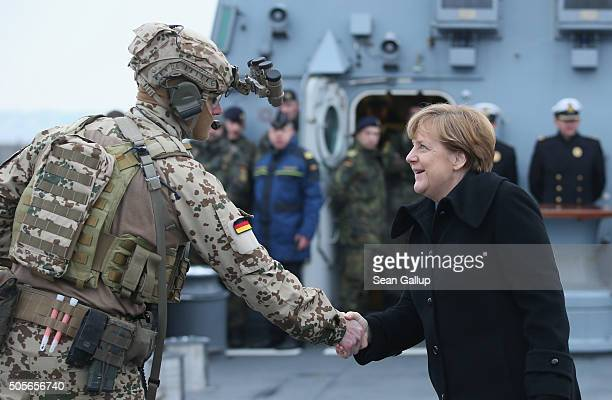 German Chancellor Angela Merkel greets a member of the German Navy's Special Forces while she visted the 'Braunschweig' warship on January 19 2016 in...