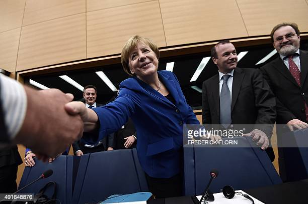German Chancellor Angela Merkel greets an unseen official as she stands with delegates as she prepares to take her seat upon arrival at the European...