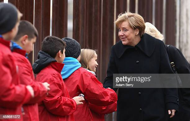 German Chancellor Angela Merkel greets children playing MP3 files through small speakers of the sounds of Mauerspechte or Berlin Wall Woodpeckers as...