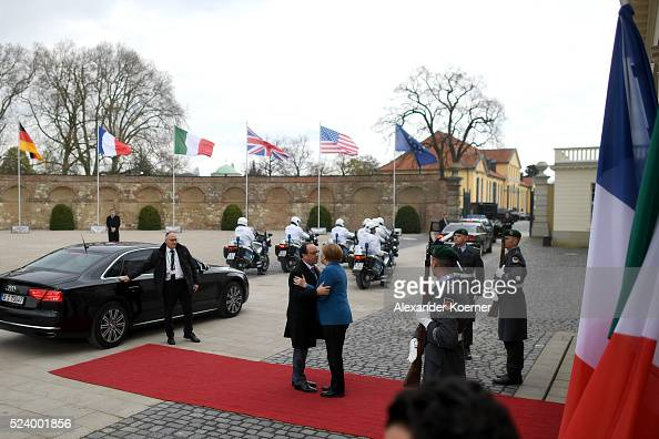 German Chancellor Angela Merkel greets France President Francois Hollande at Schloss Herrenhausen palace upon his arrival for a meeting between US...