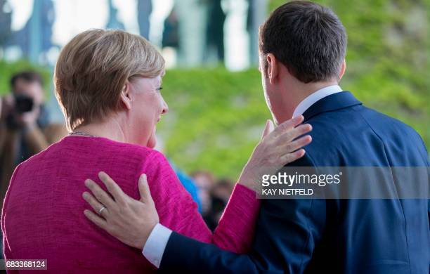 German Chancellor Angela Merkel greets French President Emmanuel Macron for talks on May 15 2017 at the chancellery in Berlin one day after the new...
