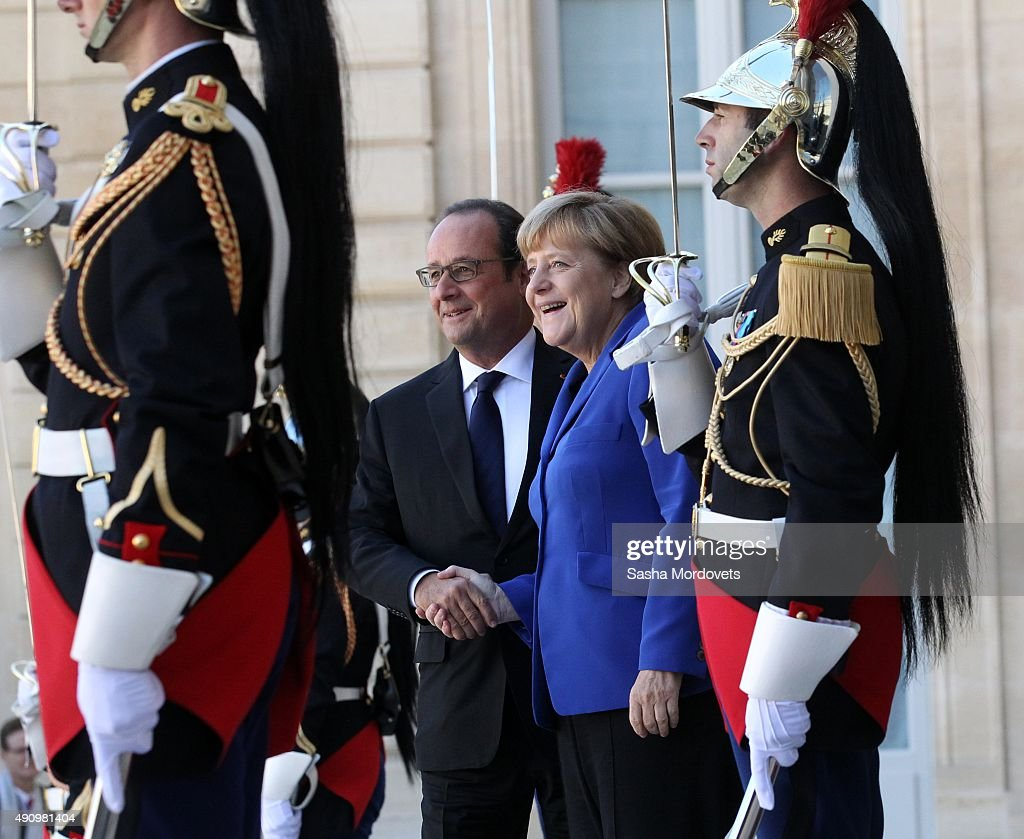 German Chancellor Angela Merkel (R) greets French President Francois Hollande (L) prior to their meeting at the Elysee Presidential Palace on October 02, 2015 in Paris, France. The leaders of France, Germany, Russia and Ukraine are meeting in Paris to consolidate a fragile peace in Ukraine, as a conflict that appears to be winding down is overshadowed by President Vladimir Putin's dramatic intervention in Syria's war.