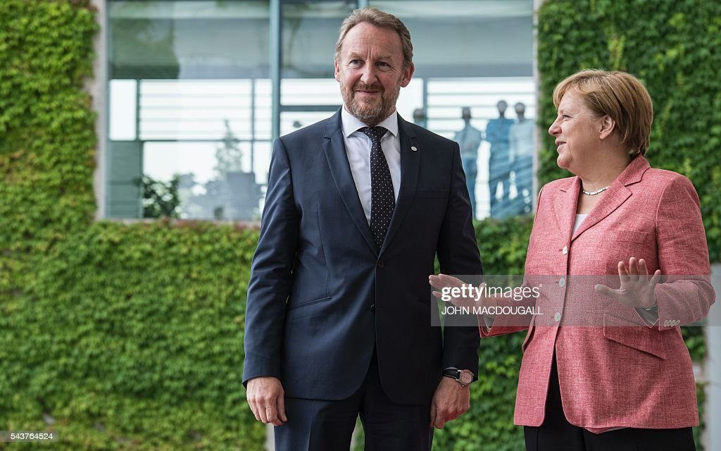 German Chancellor Angela Merkel (R) greets member of the Presidency of Bosnia and Herzegovina, Bakir Izetbegovic, during a welcoming ceremony at the chancellery in Berlin on June 30, 2016. / AFP / JOHN