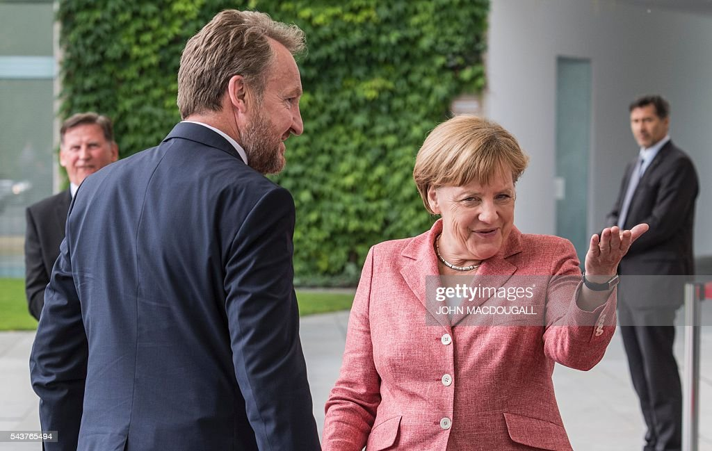 German Chancellor Angela Merkel (R) greets member of the Presidency of Bosnia and Herzegovina Bakir Izetbegovic during a welcoming ceremony at the chancellery in Berlin on June 30, 2016. / AFP / JOHN