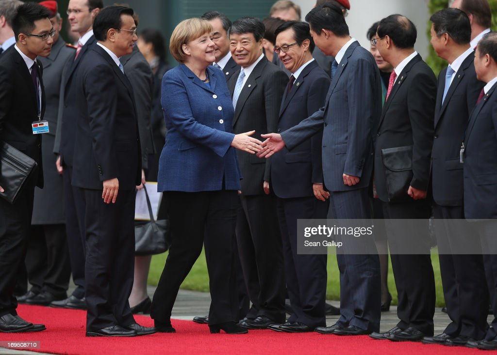 German Chancellor <a gi-track='captionPersonalityLinkClicked' href=/galleries/search?phrase=Angela+Merkel&family=editorial&specificpeople=202161 ng-click='$event.stopPropagation()'>Angela Merkel</a> (C) greets members of the Chinese government delegaiton as Chinese Prime Minister <a gi-track='captionPersonalityLinkClicked' href=/galleries/search?phrase=Li+Keqiang&family=editorial&specificpeople=2481781 ng-click='$event.stopPropagation()'>Li Keqiang</a> (L) looks on upon his arrival at the Chancellery on May 26, 2013 in Berlin, Germany. On his first official visit to Germany as prime minister, Mr. Li is scheduled to meet with German federal and regional government officials and business representatives.