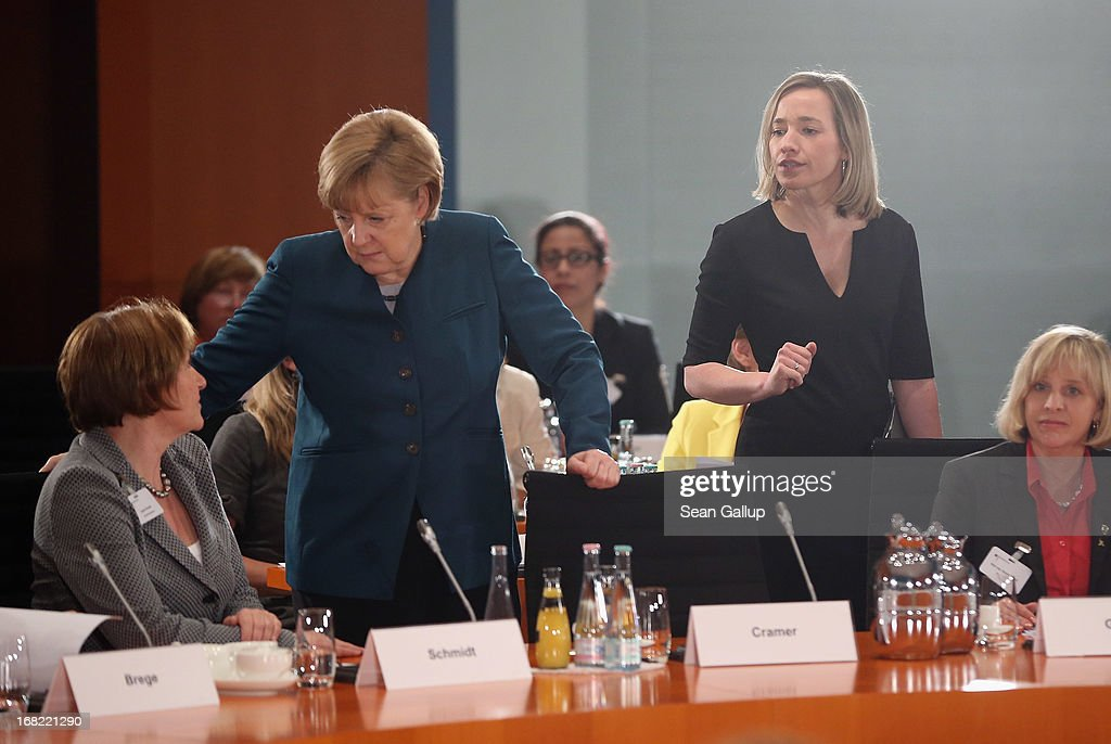 German Chancellor <a gi-track='captionPersonalityLinkClicked' href=/galleries/search?phrase=Angela+Merkel&family=editorial&specificpeople=202161 ng-click='$event.stopPropagation()'>Angela Merkel</a> (C) greets participants as German Family Minister Kristina Schroeder (R) looks on at a conference of women leaders hosted by Merkel at the Chancellery on May 7, 2013 in Berlin, Germany. German political parties are sparring over the introduction of quotas for a minimum number of women in senior management positions.
