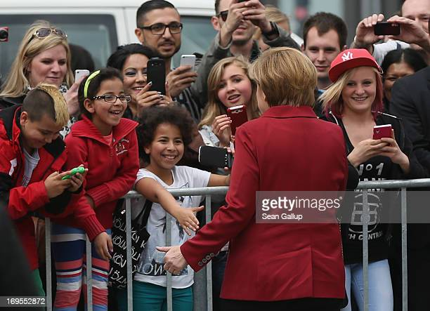 German Chancellor Angela Merkel greets school children who had gathered at the periphery at the ElectroMobility Conference at the Berlin Congress...