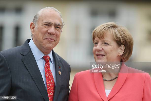 German Chancellor Angela Merkel greets SecretaryGeneral of the Organisation for Economic Cooperation and Development Jose Angel Gurria on the second...