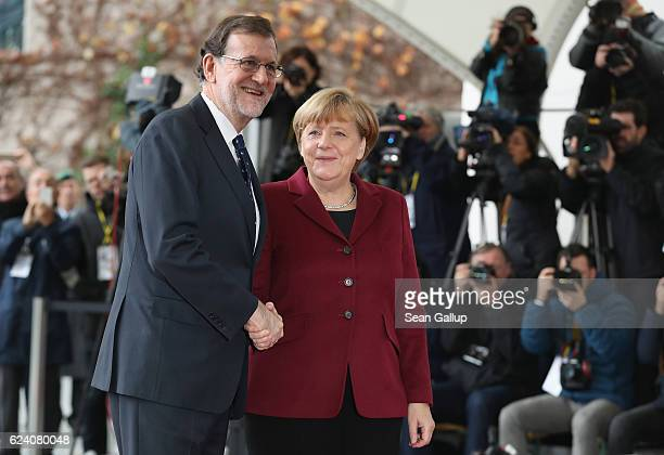 German Chancellor Angela Merkel greets Spanish Prime Minister Mariano Rajoy upon his arrival for talks between US President Barack Obama and western...