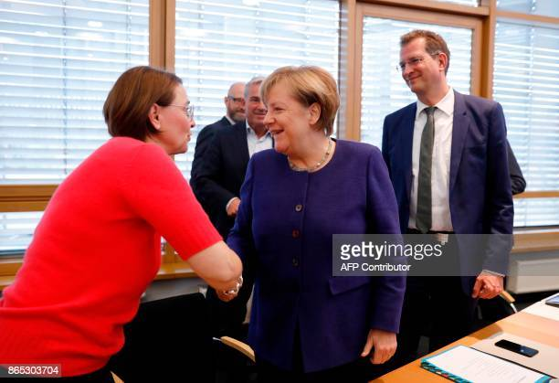 German Chancellor Angela Merkel greets staff upon arrival for a meeting of the federal executive board of the Christian Democratic Union in Berlin on...