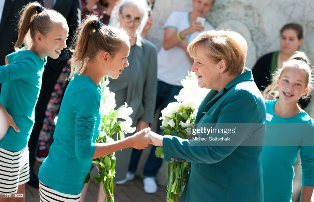 German Chancellor <a gi-track='captionPersonalityLinkClicked' href=/galleries/search?phrase=Angela+Merkel&family=editorial&specificpeople=202161 ng-click='$event.stopPropagation()'>Angela Merkel</a> greets students, including triplets Charlotte, Marlene and Elisabeth, upon her arrival at the Heinrich-Schliemann-Gymnasium high school on August 13, 2013 in Berlin, Germany. Merkel visited the school to speak to 12th grade high school students about the construction of the Berlin Wall in 1961. Today is the 52nd anniversary of the construction of the Wall by the communist East German government that divided Berlin into East and West and became an icon of the Cold War.