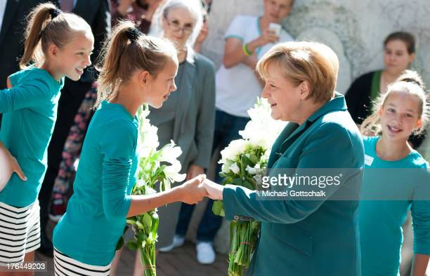German Chancellor Angela Merkel greets students including triplets Charlotte Marlene and Elisabeth upon her arrival at the...
