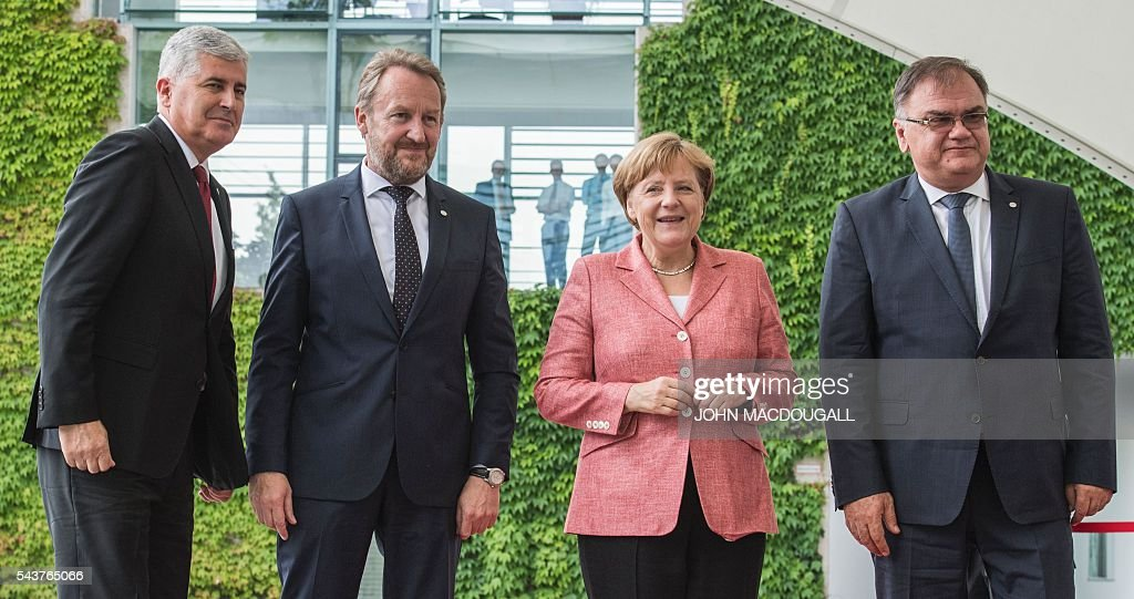 German Chancellor Angela Merkel (2nd from R) greets the three members of the Presidency of Bosnia and Herzegovina Dragan Covic (L), Bakir Izetbegovic (2nd from L) and Mladen Ivanic (R) during a welcoming ceremony at the chancellery in Berlin on June 30, 2016. / AFP / JOHN