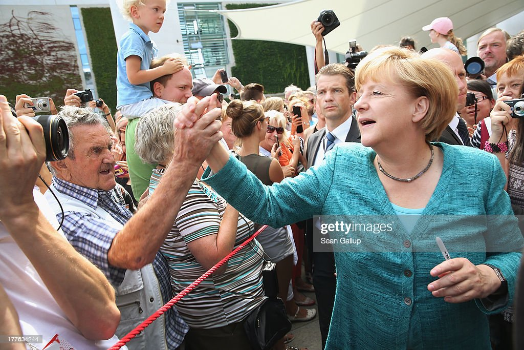 German Chancellor <a gi-track='captionPersonalityLinkClicked' href=/galleries/search?phrase=Angela+Merkel&family=editorial&specificpeople=202161 ng-click='$event.stopPropagation()'>Angela Merkel</a> greets visitors during the annual open-house day at the Chancellery on August 25, 2013 in Berlin, Germany. Germany is facing federal elections scheduled for September 22 and so far the CDU has a substantial lead in polls over the opposition.