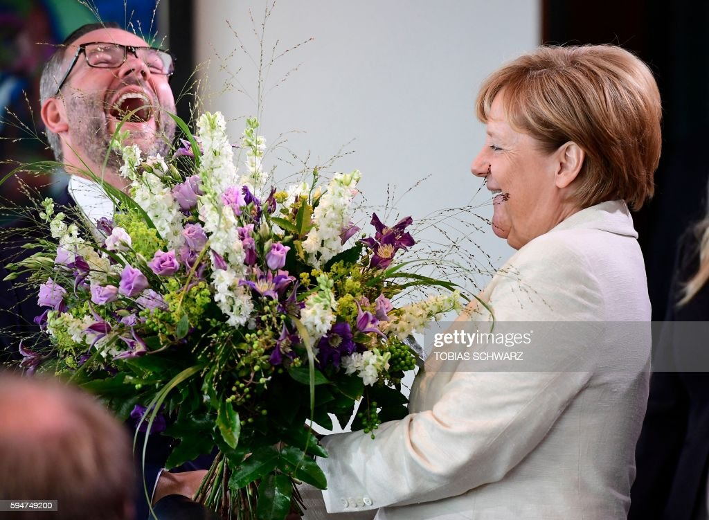 TOPSHOT German Chancellor Angela Merkel hands over birthday flowers to State Minister at the Foreign Ministry Michael Roth before the weekly cabinet...