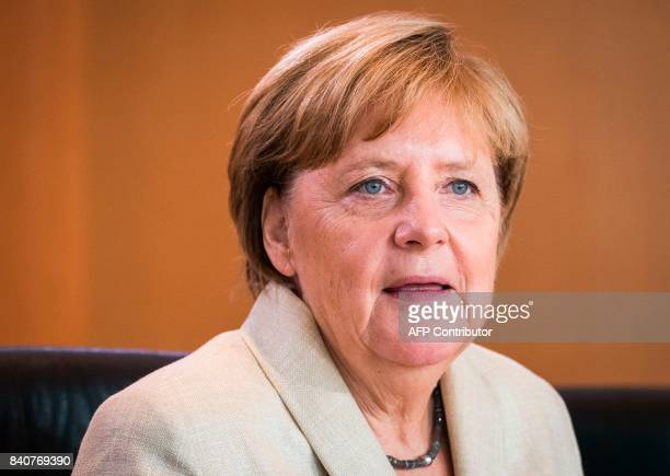 German Chancellor Angela Merkel has taken seat to lead the weekly cabinet meeting on August 30 2017 at the Chancellery in Berlin / AFP PHOTO / Odd...