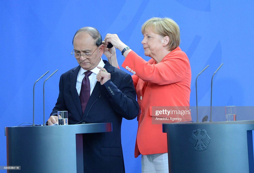 German Chancellor Angela Merkel (R) helps the President of Myanmar, Thein Sein (L) to put on his headphones at the beginning of press conference at the Chancellery in Berlin, Germany on September 03, 2014.