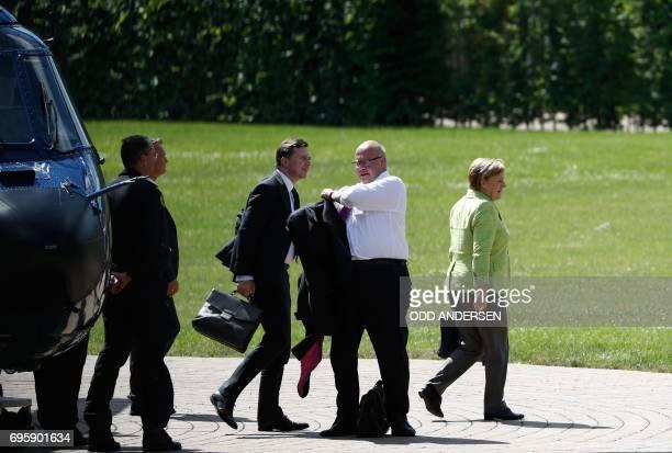 German Chancellor Angela Merkel her spokesman Steffen Seibert and German Chief of Staff Peter Altmaier arrive by helicopter at the German...