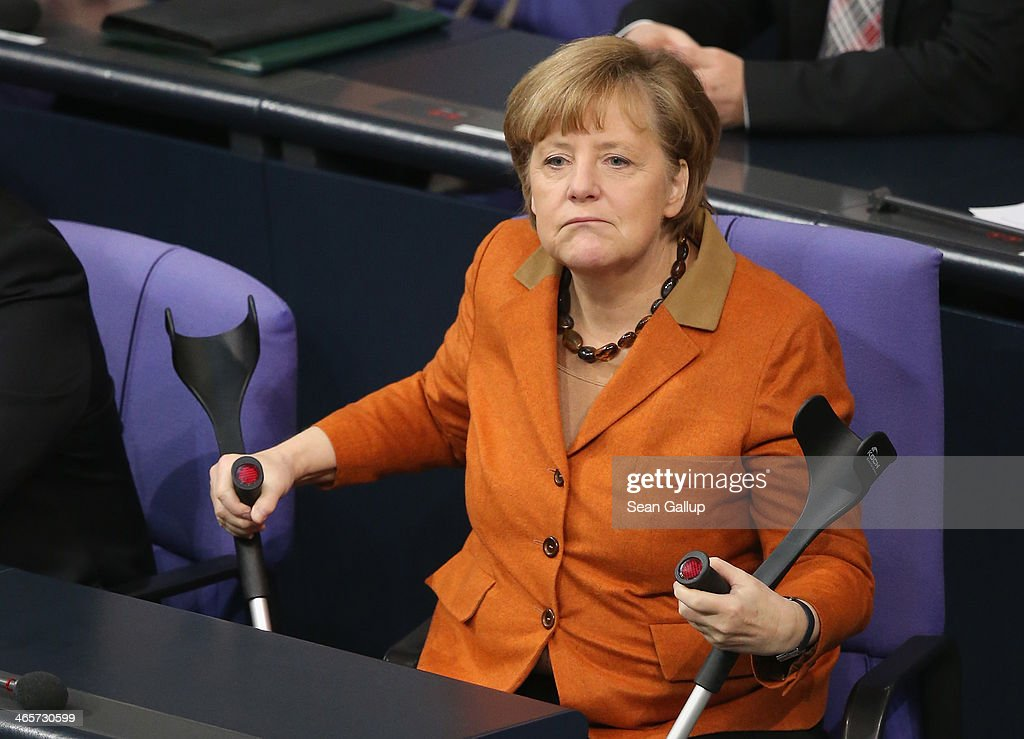 German Chancellor <a gi-track='captionPersonalityLinkClicked' href=/galleries/search?phrase=Angela+Merkel&family=editorial&specificpeople=202161 ng-click='$event.stopPropagation()'>Angela Merkel</a>, holding crutches due to an injury, arrives to give a government declaration to outline the policy priorities of the new German coalition government of Christian Democrats and Social Democrats on January 29, 2104 in Berlin, Germany. The new government was sworn in in December and has a strong majority in the Bundestag to push through legislation.