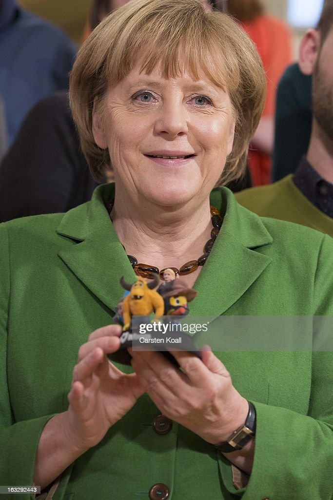 German Chancellor <a gi-track='captionPersonalityLinkClicked' href=/galleries/search?phrase=Angela+Merkel&family=editorial&specificpeople=202161 ng-click='$event.stopPropagation()'>Angela Merkel</a>, holds 3D printed characters, during a visit in a guided tour in the Wooga company, which makes social games for smartphones and tablets, on March 7, 2013 in Berlin, Germany. Berlin has drawn a significant number of startup companies in recent years, many of which are drawn by the city's hip reputation and its comparatively low cost of living.