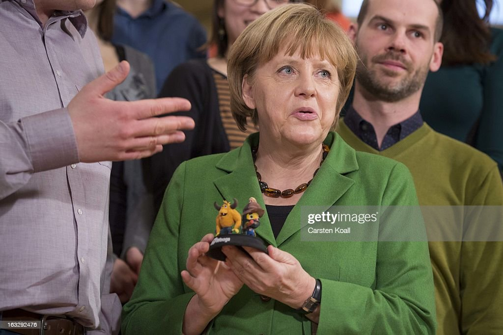 German Chancellor Angela Merkel, holds 3D printed characters, during a visit in a guided tour in the Wooga company, which makes social games for smartphones and tablets, on March 7, 2013 in Berlin, Germany. Berlin has drawn a significant number of startup companies in recent years, many of which are drawn by the city's hip reputation and its comparatively low cost of living.