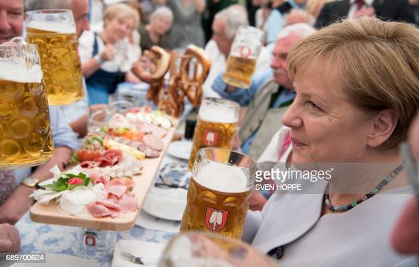 German Chancellor Angela Merkel holds a glass of beer as she attends an election campaign event of the Christian Social Union Bavarian sister party...