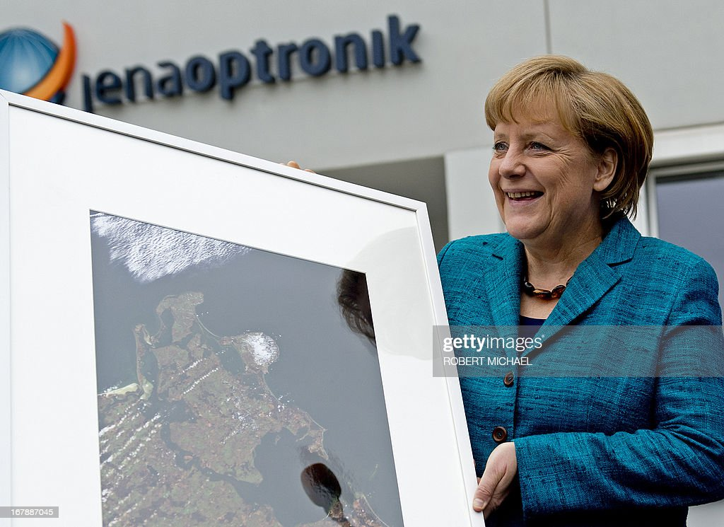 German Chancellor Angela Merkel holds a picture of Baltic Sea Island of Ruegen after a visit of the Jena-Optronik GmbH (Ltd), a German provider of opto-electronic instruments and sub-systems for space applications, on May 2 , 2013 in Jena, eastern Germany. AFP PHOTO / ROBERT MICHAEL