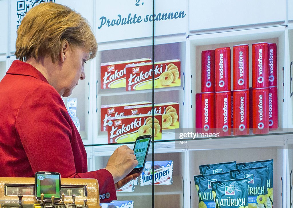 German Chancellor Angela Merkel holds a smartphone to test a porduct scanner at the booth of German telecommunication company Vodafone during the opening event of the world's largest computer expo CeBIT high-tech fair on March 5, 2013 in Hanover, central Germany. Poland is this year's partner country of the fair running from March 5 to 9, 2013. AFP PHOTO / CARSTEN KOALL