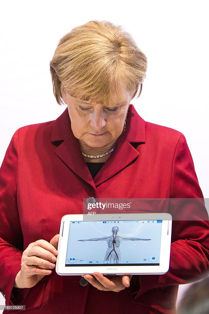 German Chancellor Angela Merkel holds a tablet device at the booth of Samsung Electronics during the opening event of the world's largest computer expo CeBIT high-tech fair on March 5, 2013 in Hanover, central Germany. Poland is this year's partner country of the fair running from March 5 to 9, 2013. AFP PHOTO / CARSTEN KOALL
