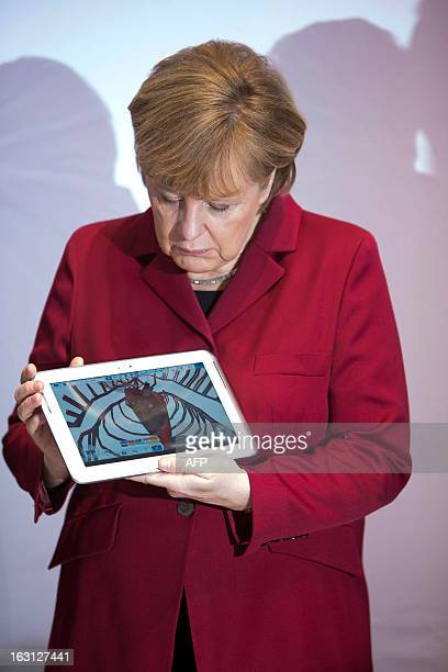 German Chancellor Angela Merkel holds a tablet device at the booth of Samsung Electronics during the opening event of the world's largest computer...