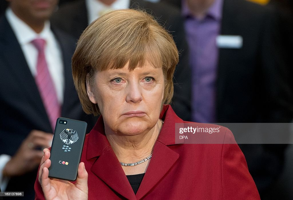 German Chancellor Angela Merkel holds a tapping proof BlackBerry mobile device at the stand of Secusmart as she tours the CeBIT high-tech fair during the opening event of the world's largest computer expo on March 5, 2013 in Hanover, central Germany. Poland is this year's partner country of the fair running from March 5 to 9, 2013.