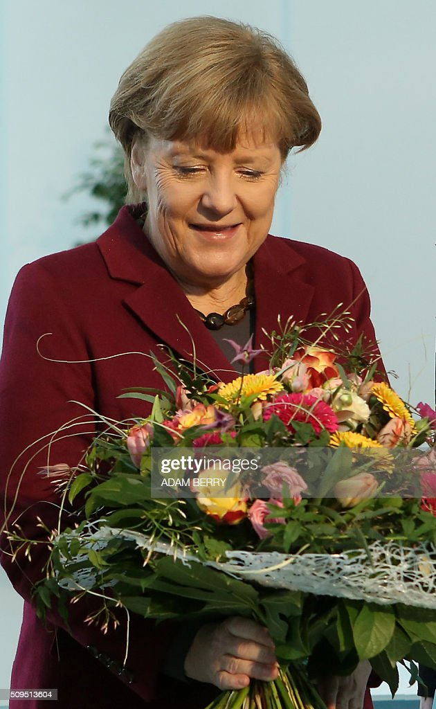 German Chancellor Angela Merkel holds a Valentine's Day bouquet of flowers she got from a Gardener's Association at the Chancellery in Berlin on February 11, 2016. / AFP / Adam BERRY
