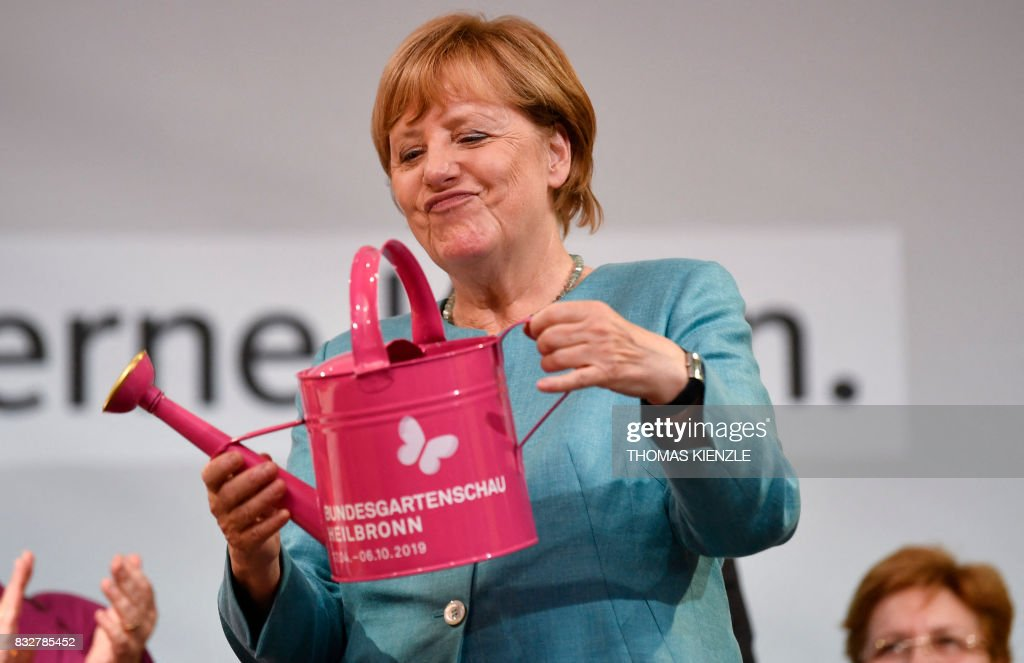 German Chancellor Angela Merkel holds a watering can she got as a gift during an election campaign rally of the Christian Democratic Union (CDU) in Heilbronn, southern Germany on August 16, 2017. /