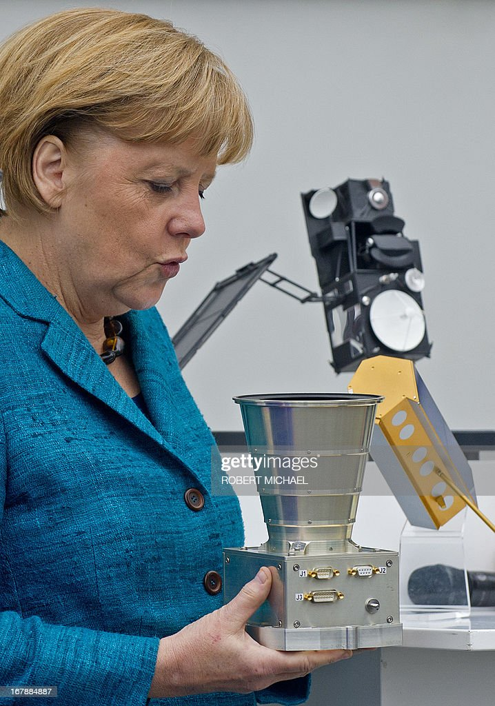 German Chancellor Angela Merkel holds an Autonomous Star Sensor, a flight proven sensor autonomous star tracking system for long-term GEO and LEO missions for telecommunication, science and Earth observation satellites during a visit at the Jena-Optronik GmbH (Ltd) on May 2 , 2013 in Jena, eastern Germany. AFP PHOTO / ROBERT MICHAEL