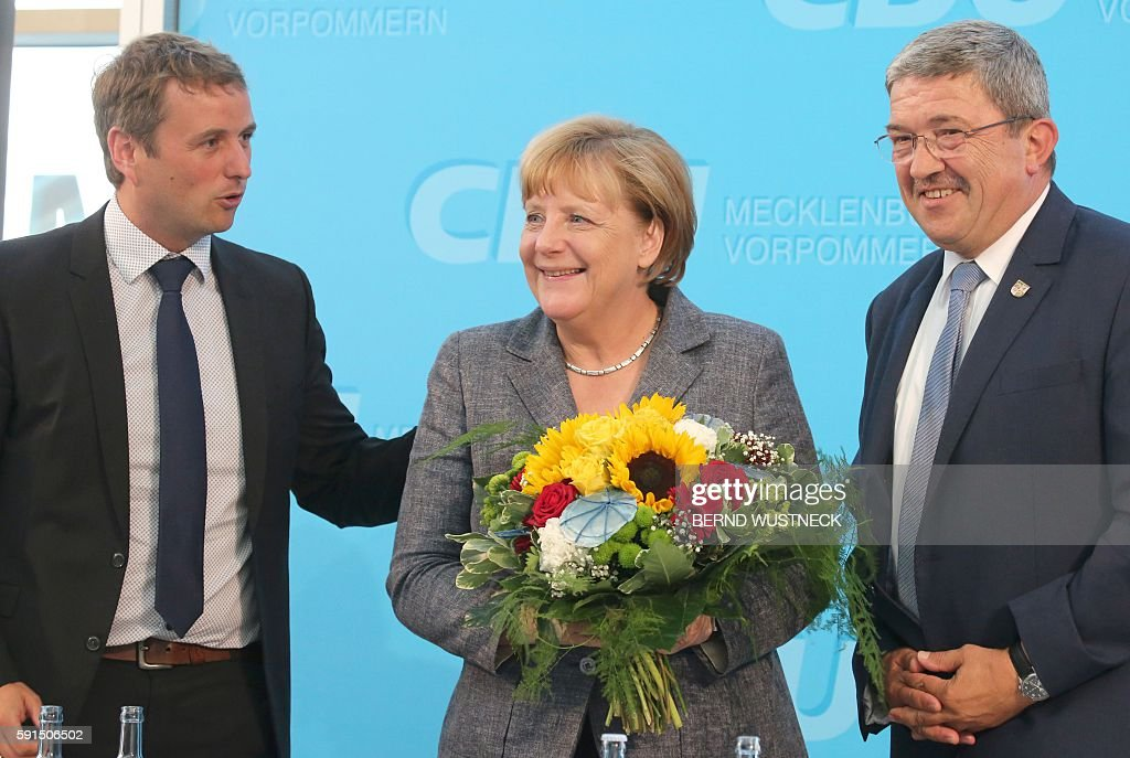 German chancellor Angela Merkel holds flowers after an election campaign of the Christian Democratic Union next to Regional general secretary Vincent...