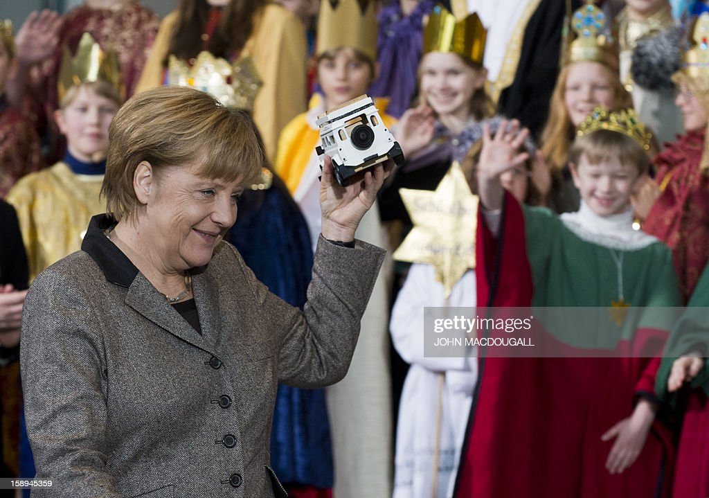 German Chancellor Angela Merkel holds up a model ambulance given to her by young Carol singers as she takes leave of them at the Chancellery in Berlin on January 4 , 2013. Carol singers visited the Chancellery as part of the 'Three King's Action' charity which focused on healthcare in Tanzania this year.
