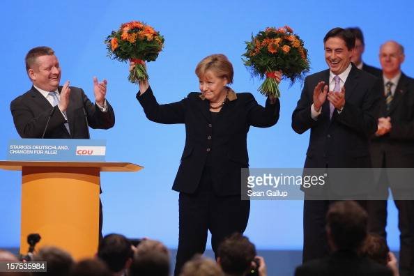 German Chancellor Angela Merkel holds up flowers after she was reelected Chairwoman of the German Christian Democratic Union with nearly 98% of...